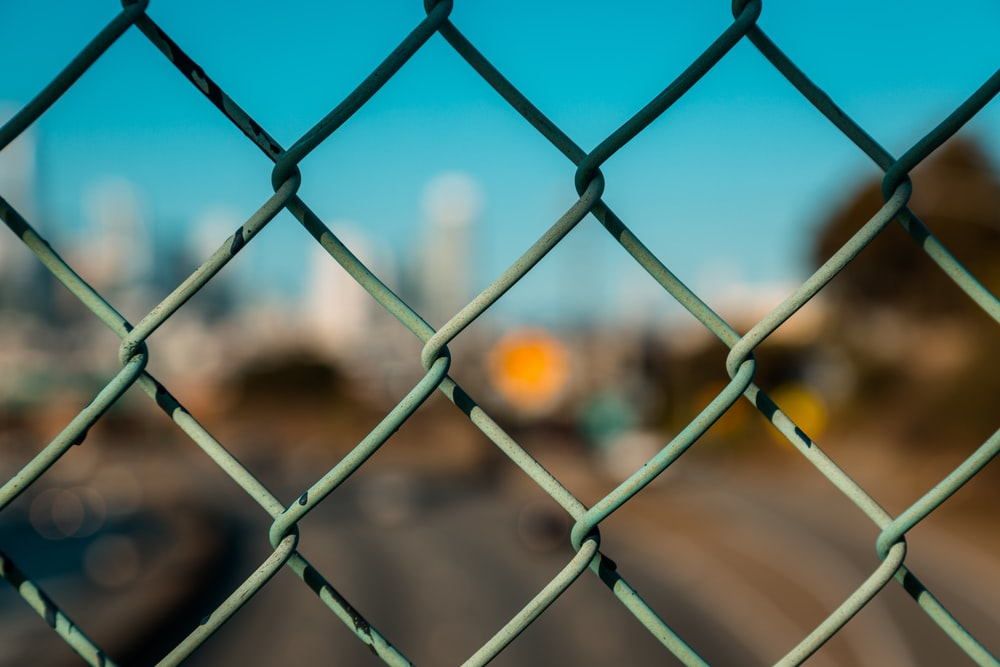grey metal fence with yellow and black car in the distance