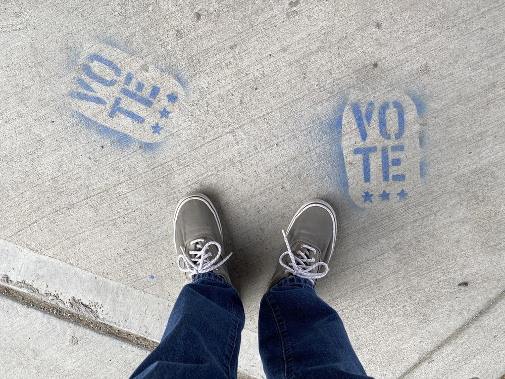 person in blue denim jeans and white sneakers standing on gray concrete floor