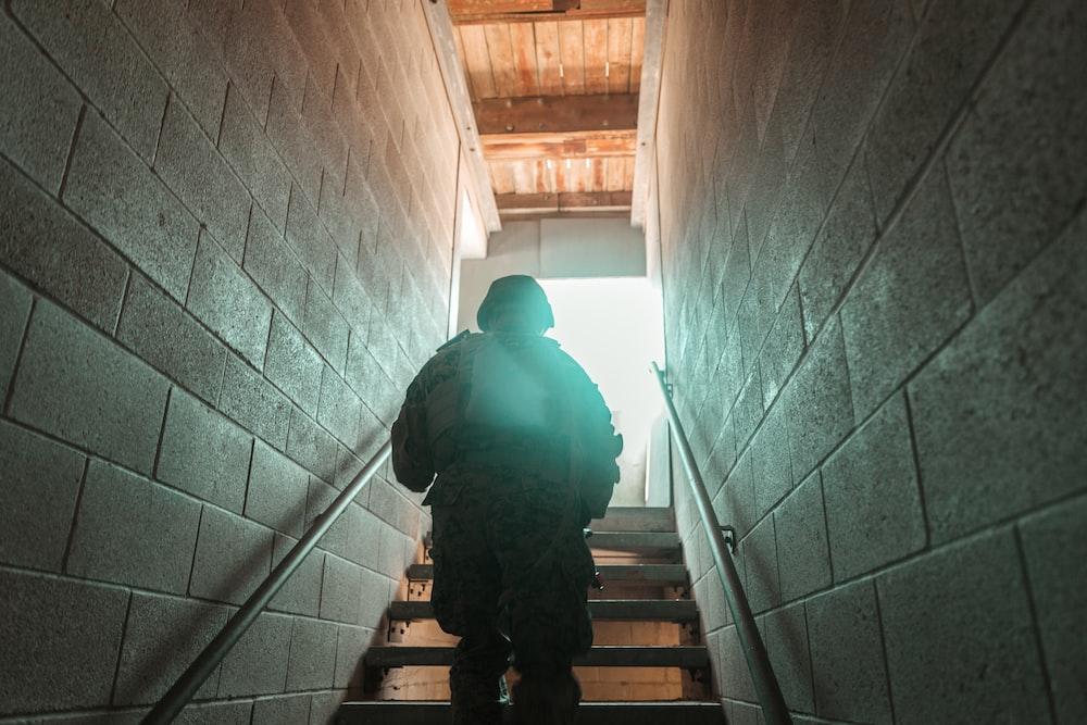man in black jacket walking on staircase