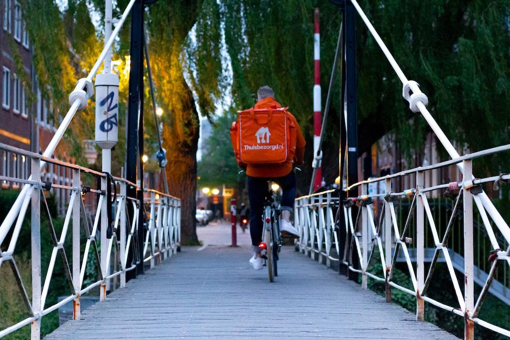 man in red jacket riding bicycle on bridge during daytime