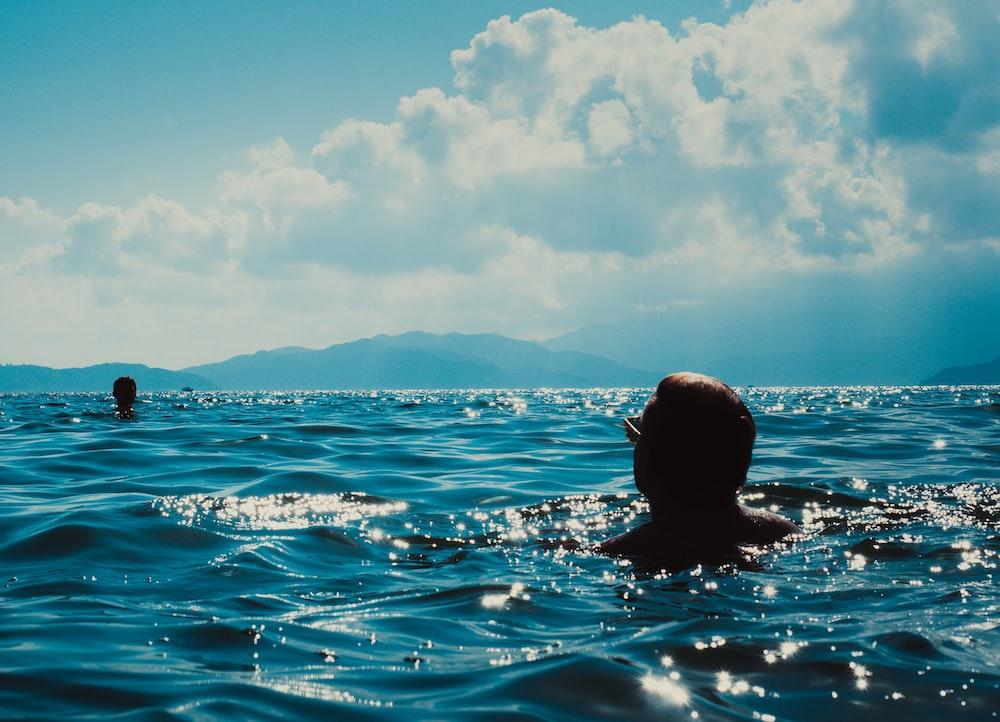 man swimming on blue sea during daytime