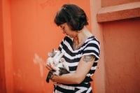 woman in black and white stripe shirt carrying white cat
