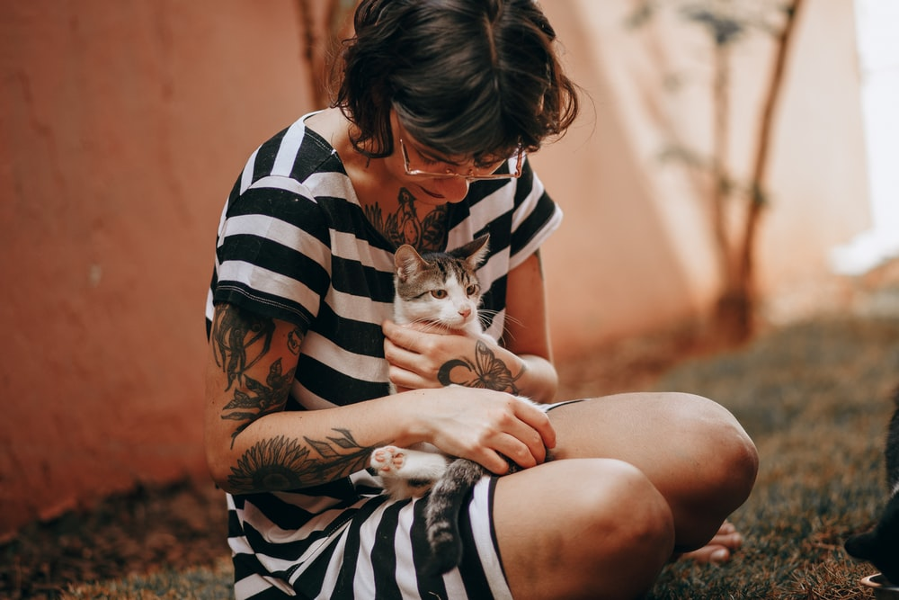woman in black and white stripe shirt hugging white and black cat