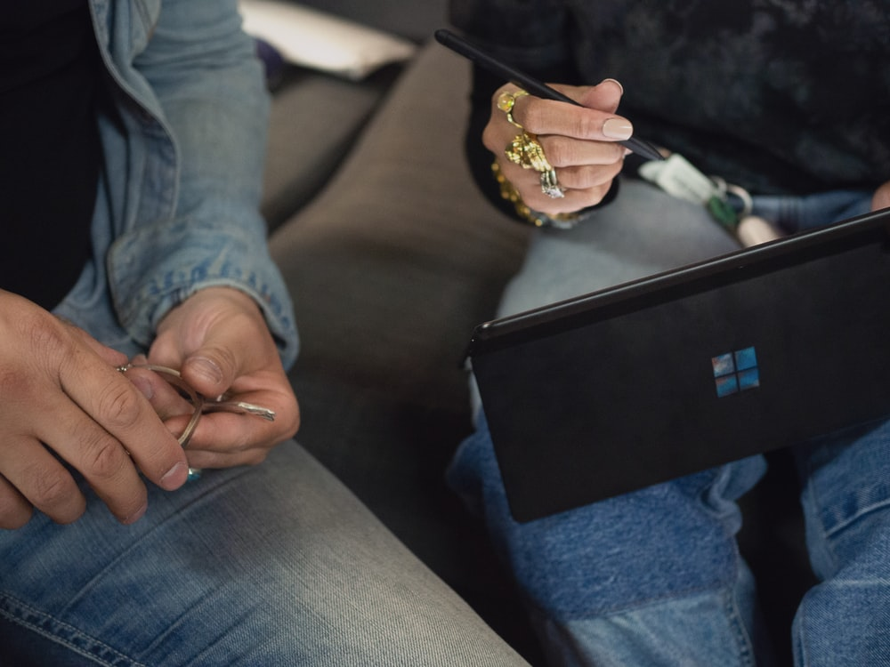 person in blue denim jeans holding Surface device