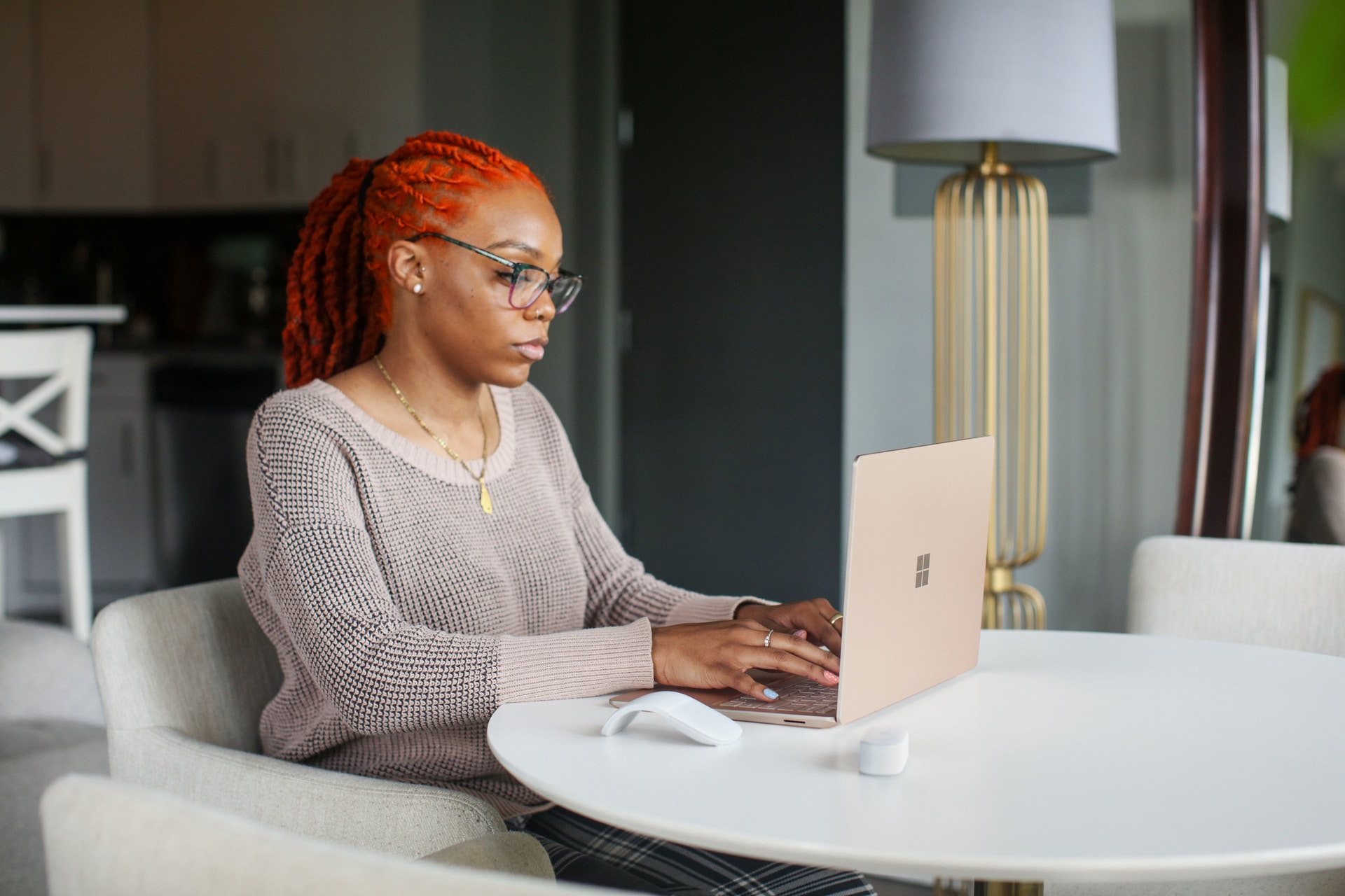 woman in gray knit sweater using Surface computer