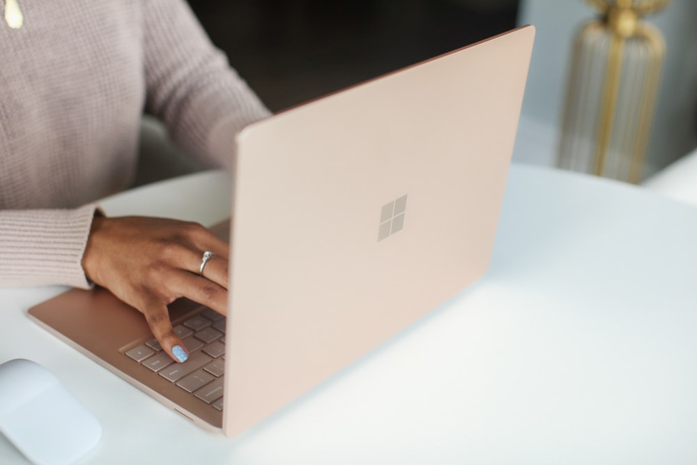 person in gray long sleeved shirt using Surface laptop