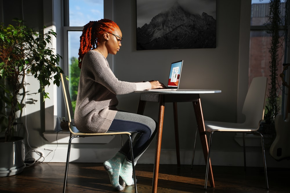 woman in gray sweater sitting on chair using laptop computer