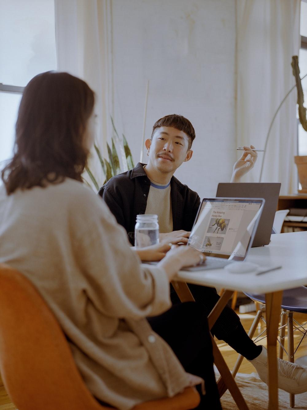 woman in white long sleeve shirt sitting beside boy in black shirt