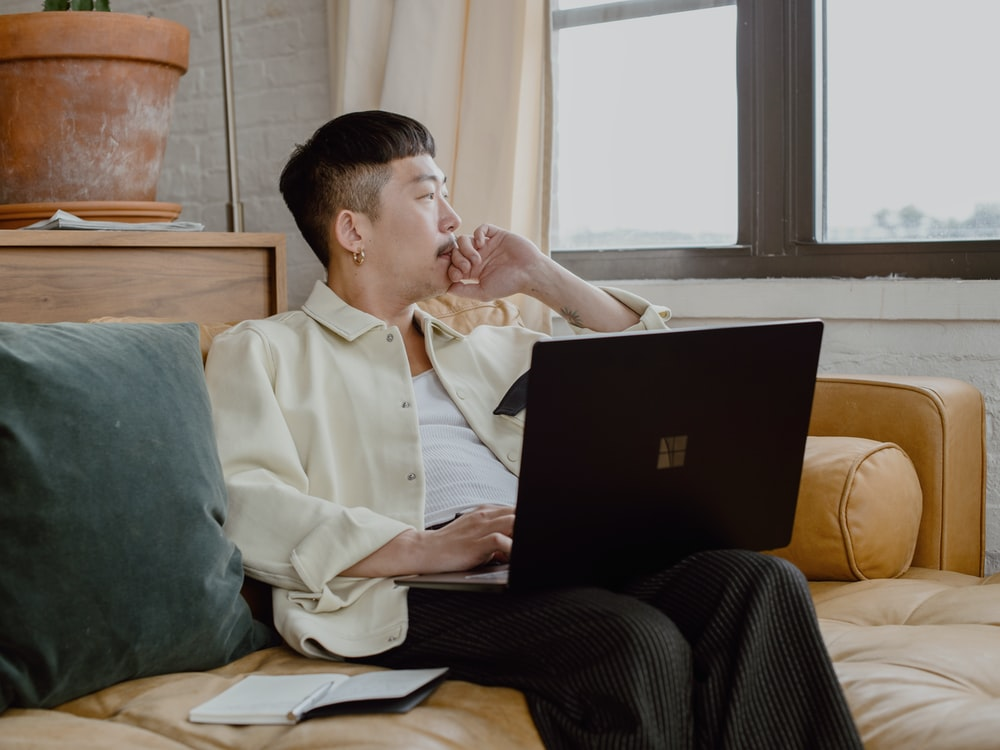 man in white dress shirt and black pants sitting on couch using Surface laptop