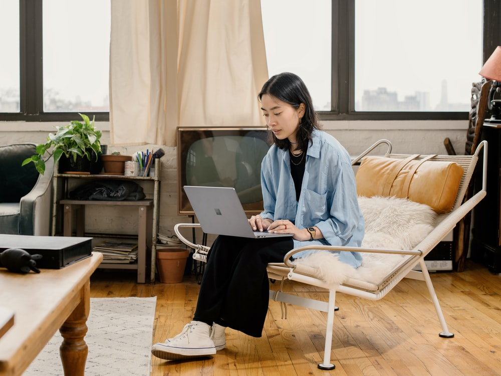 woman in blue shirt sitting on white chair using Surface laptop