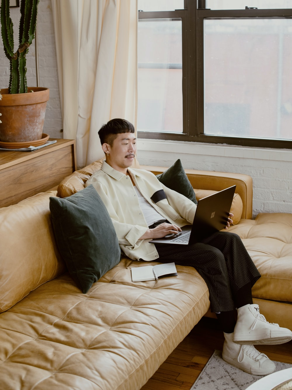 man in white dress shirt sitting on white couch using black Surface laptop
