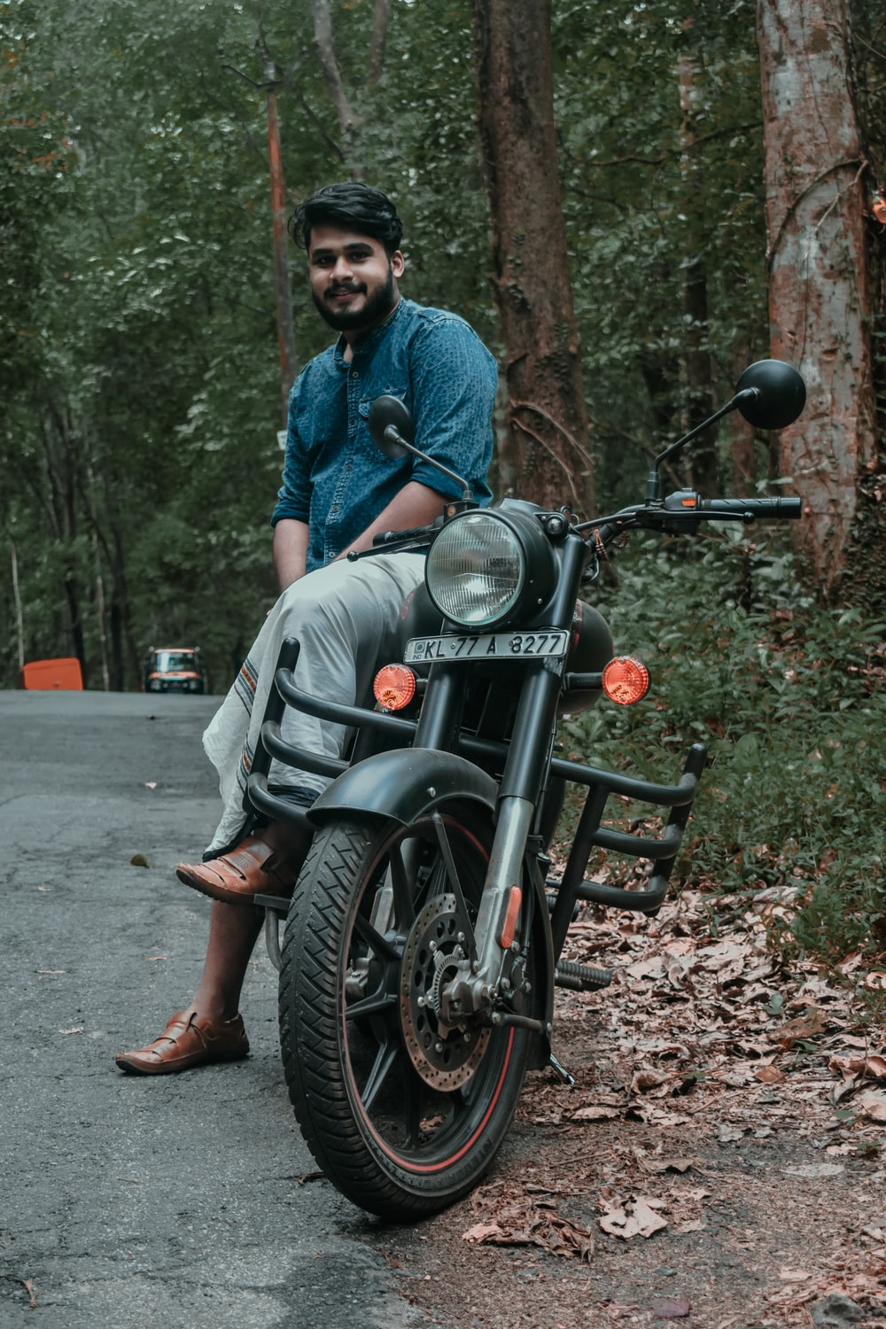 man in blue dress shirt and gray pants sitting on black motorcycle