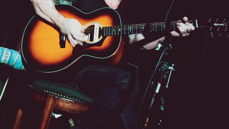 man in black tank top playing acoustic guitar