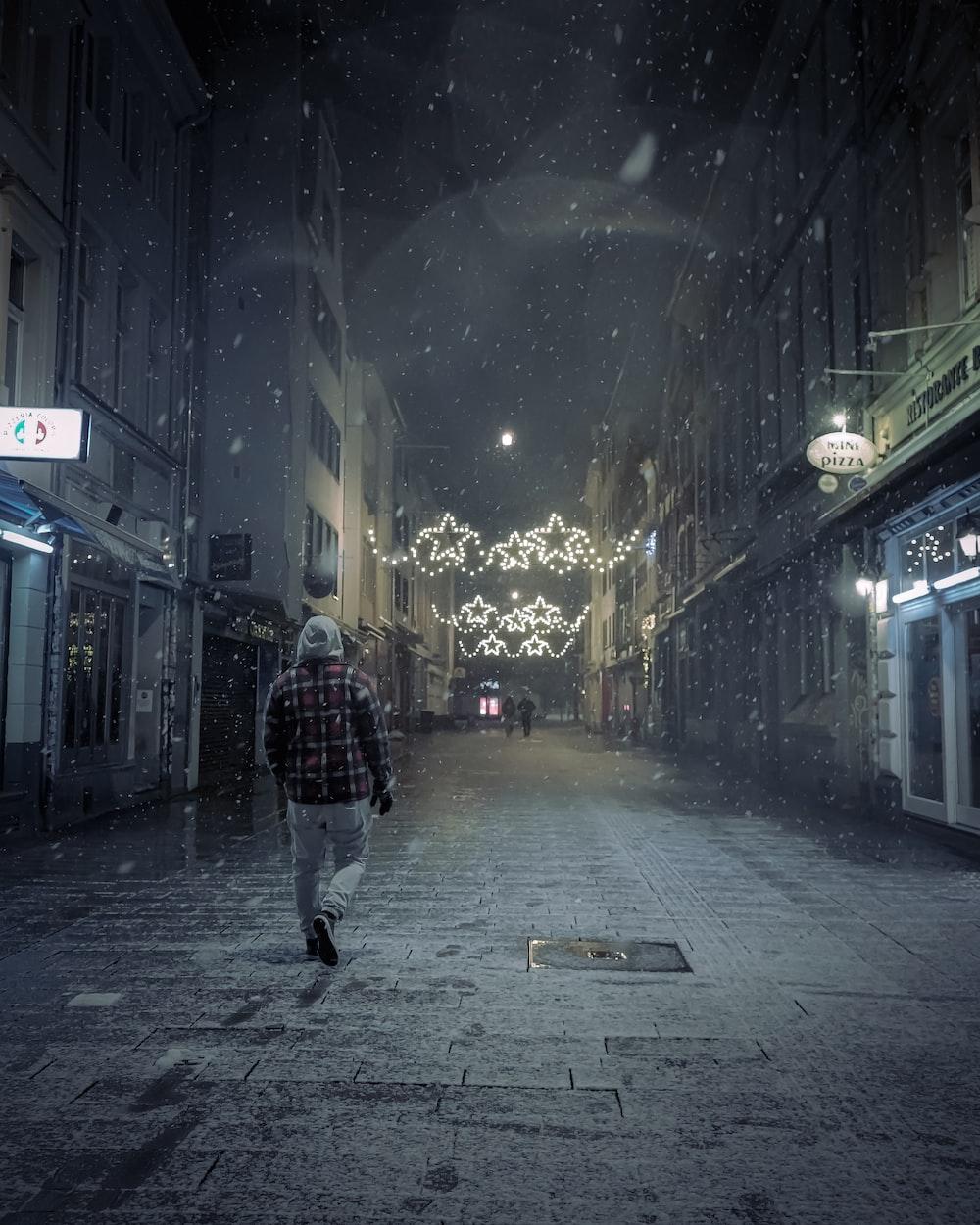 man in black jacket walking on street during nighttime