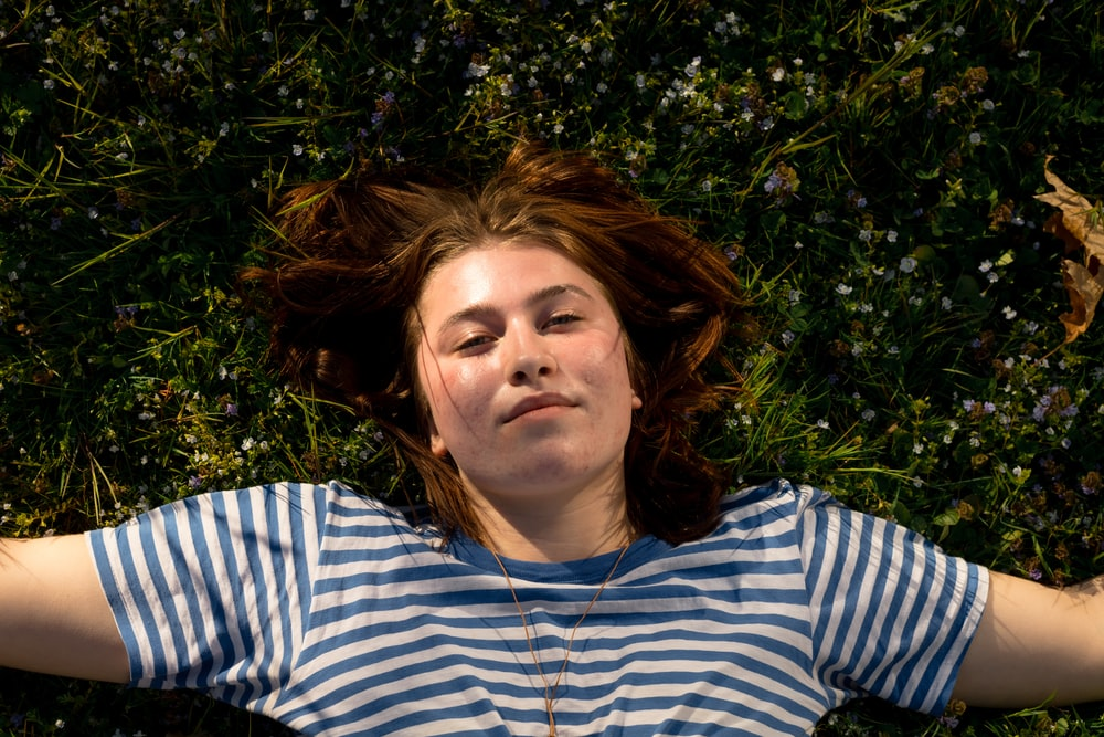 woman in white and blue striped shirt lying on green grass