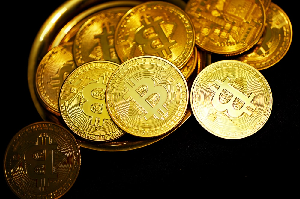 gold round coins on black surface