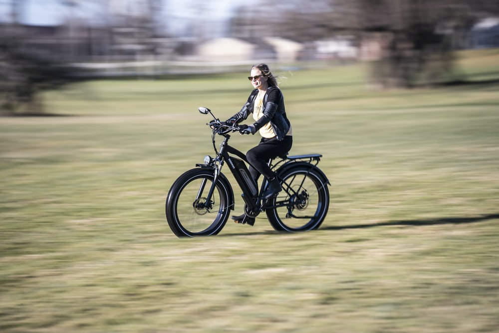 woman in black jacket riding on black motorcycle on green grass field during daytime