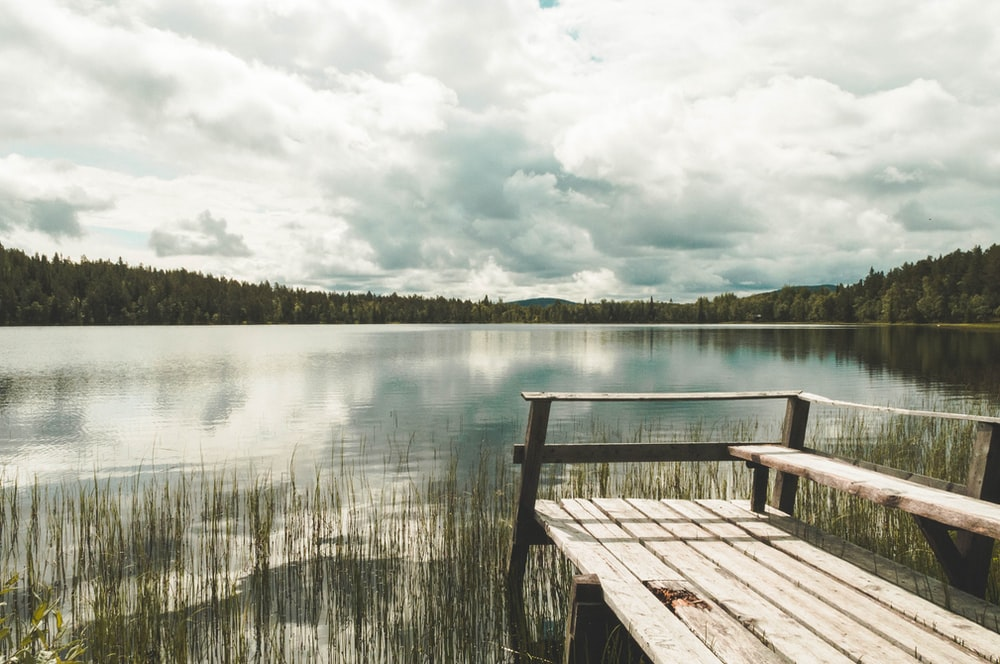 brown wooden dock on lake under white clouds during daytime