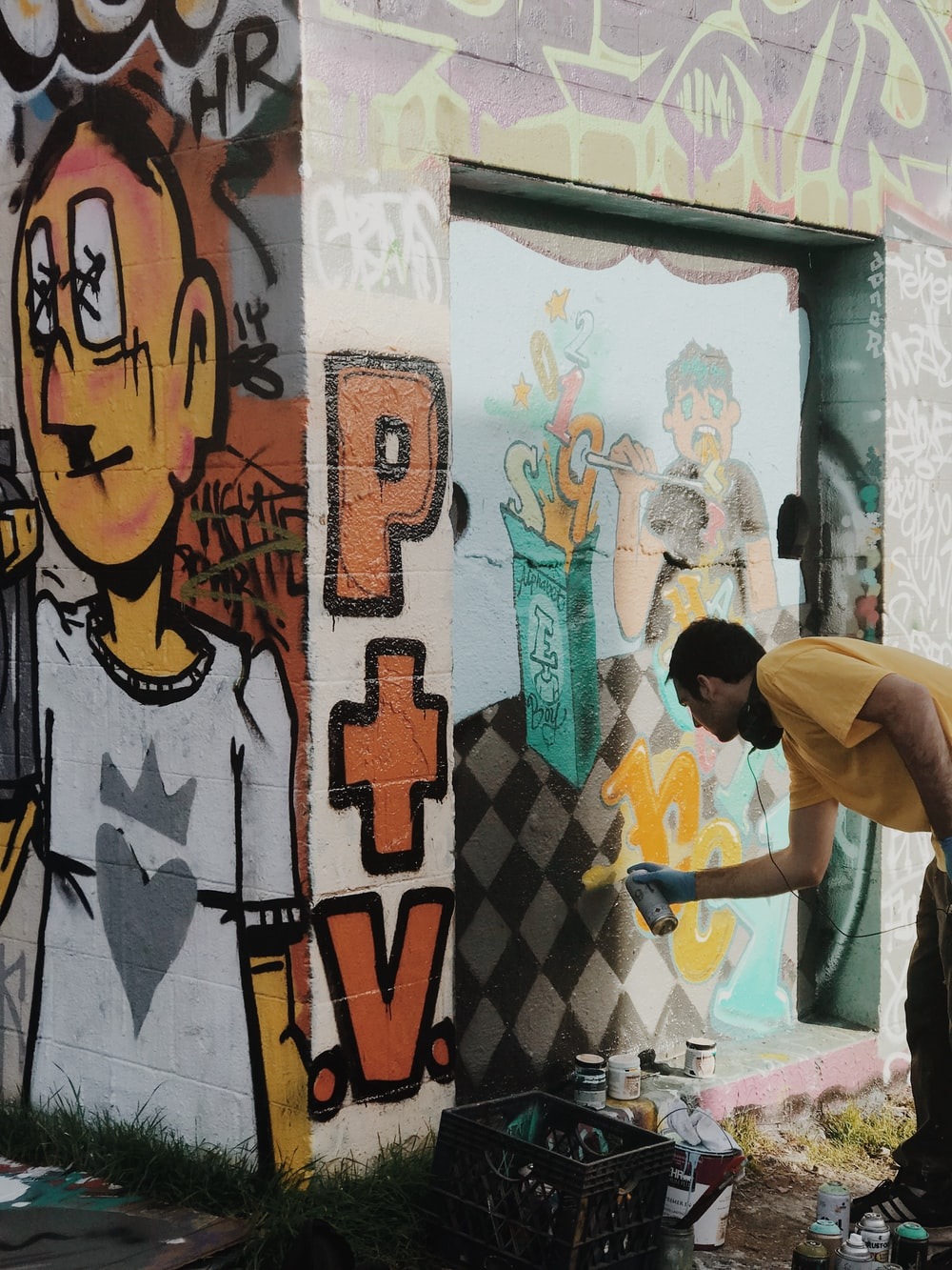 man in white t-shirt standing near wall with graffiti