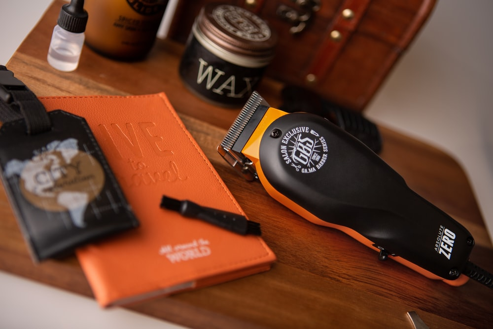 orange book beside black and white round container on brown wooden table