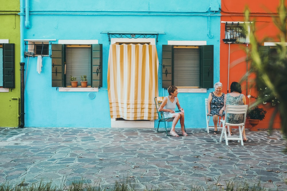 3 women sitting on white plastic chairs in front of blue and teal concrete house during