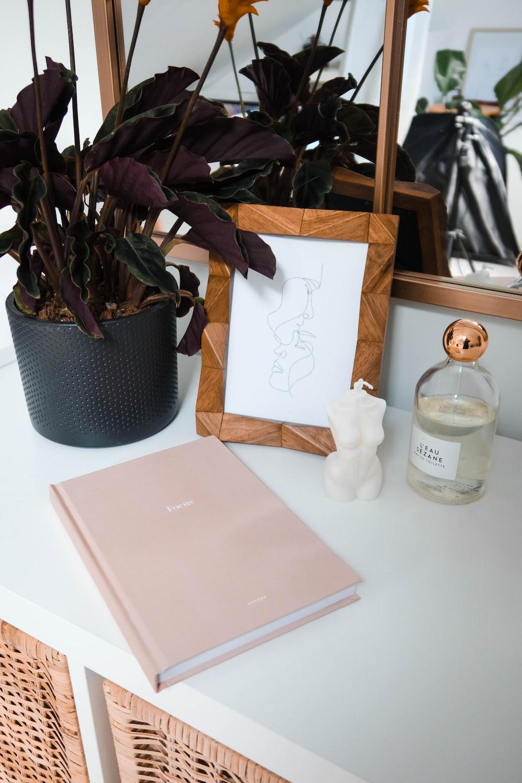 white ceramic angel figurine beside pink book