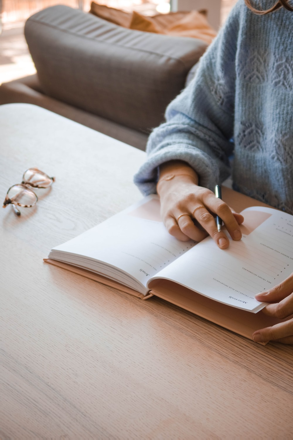 person in gray sweater holding white book