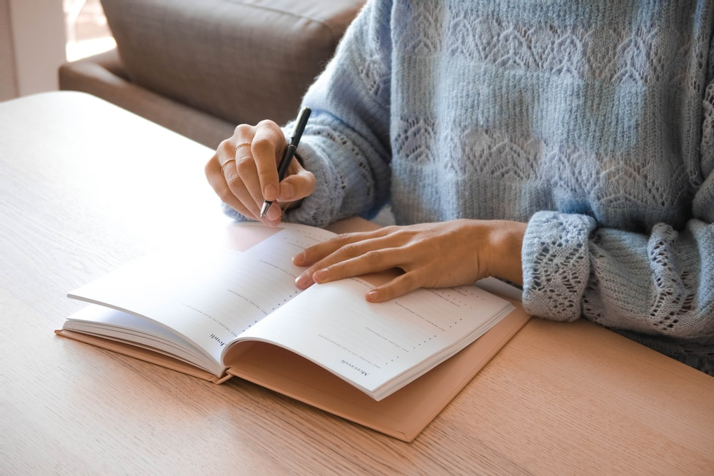 woman in white and gray sweater writing on white paper