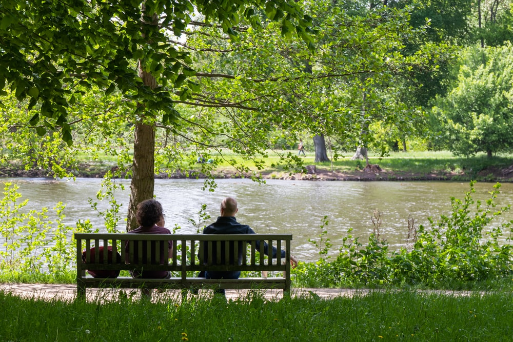 2 women sitting on bench near body of water during daytime