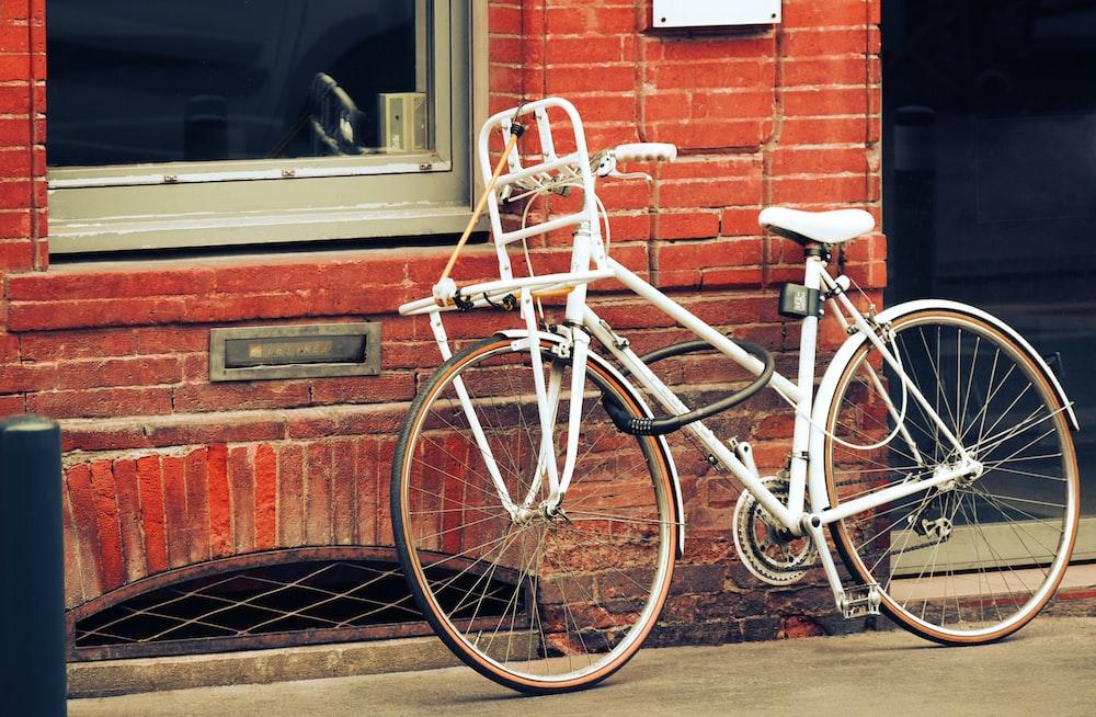 white city bike parked beside brown brick wall