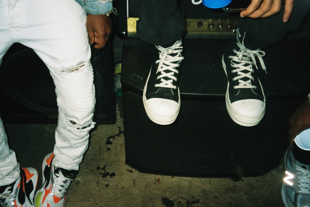 person wearing black and white converse all star high top sneakers