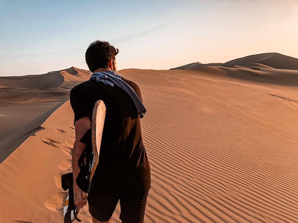 man in black jacket walking on desert during daytime