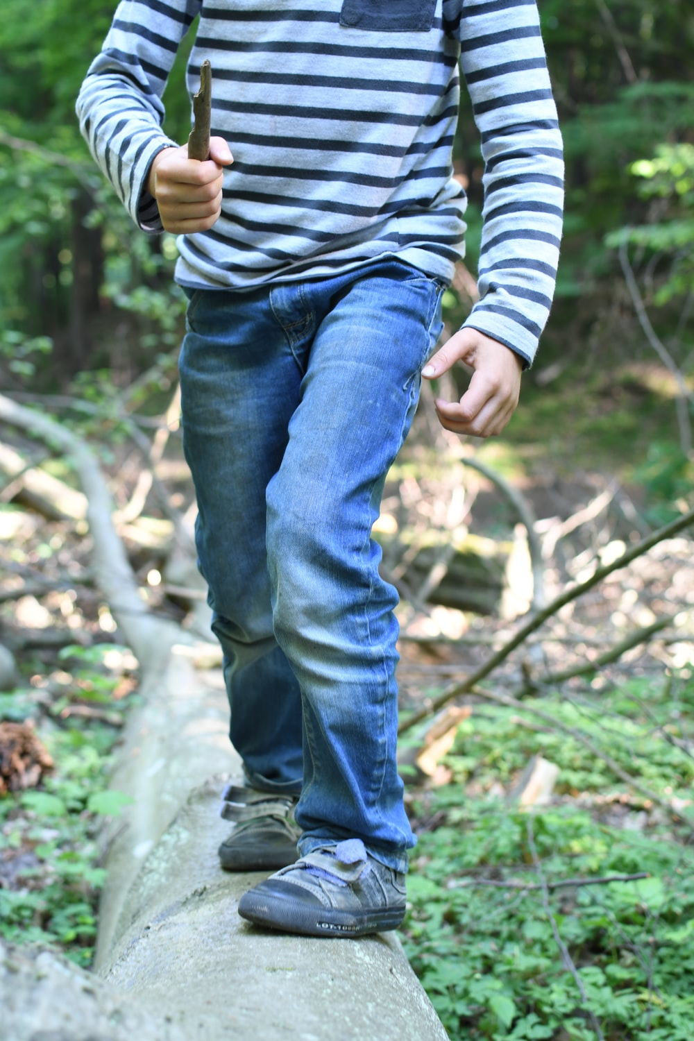man in blue denim jeans and white and black striped long sleeve shirt