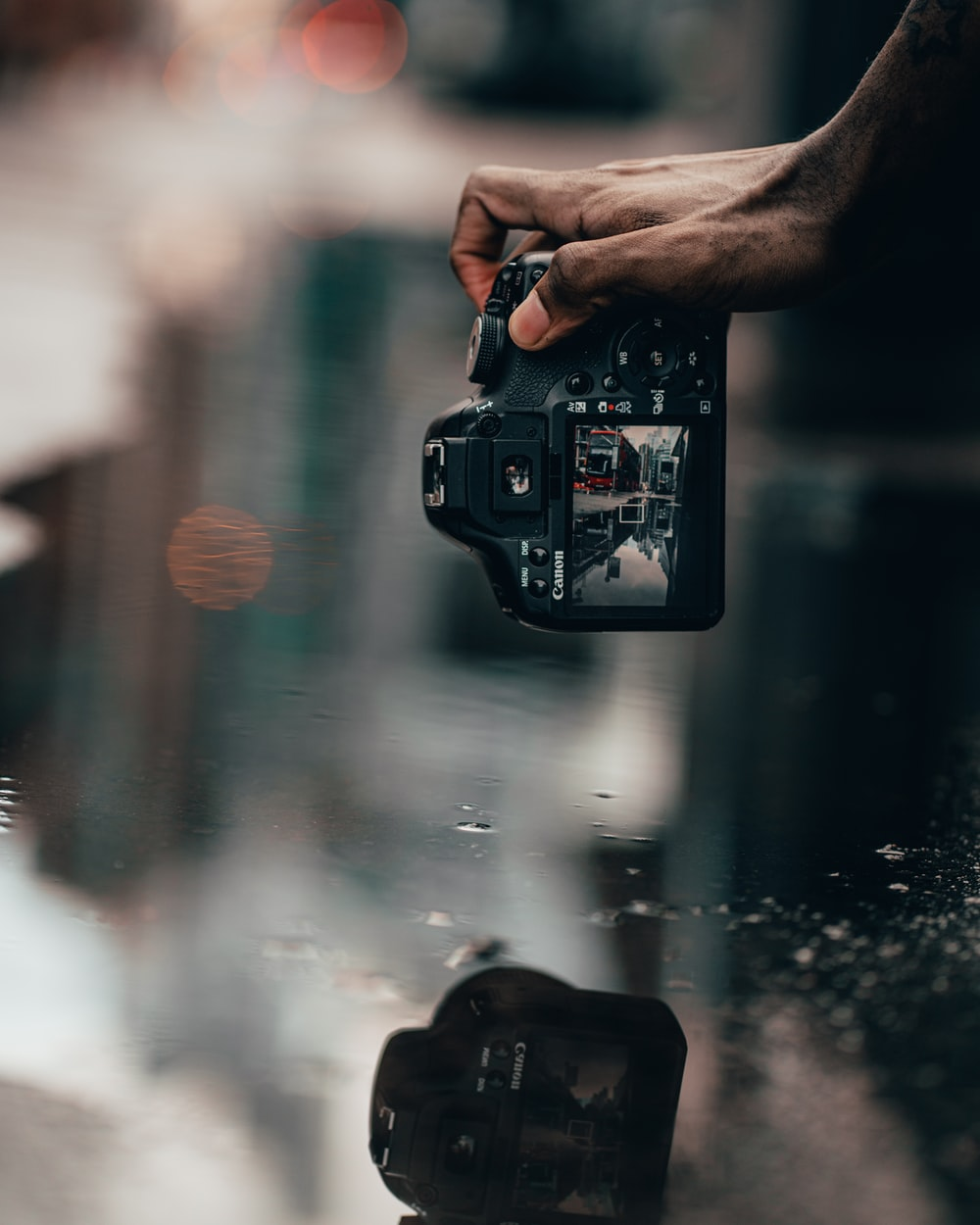 person taking photo of water droplets on glass