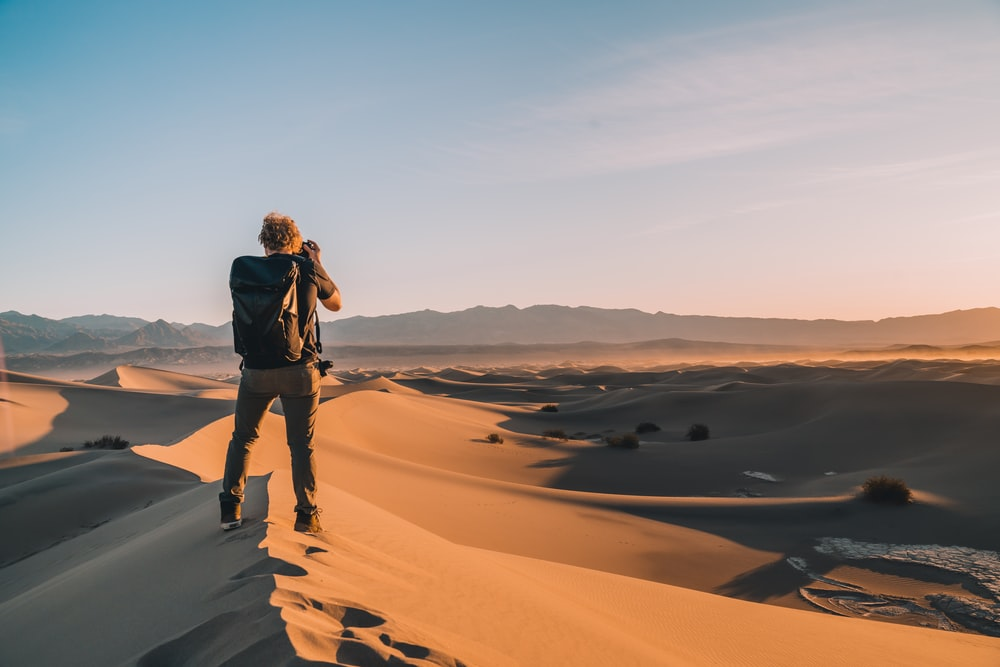 woman in black jacket standing on brown sand during daytime
