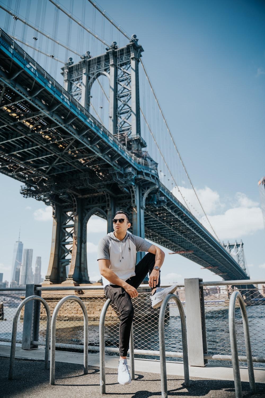 man in white shirt sitting on bicycle near bridge during daytime