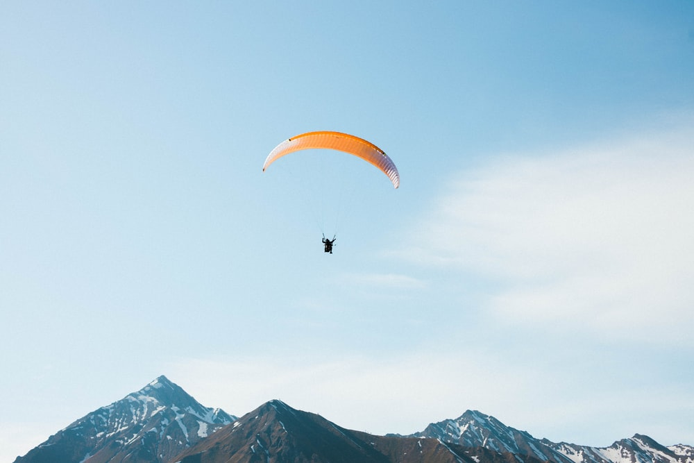 person riding orange parachute over the mountains during daytime
