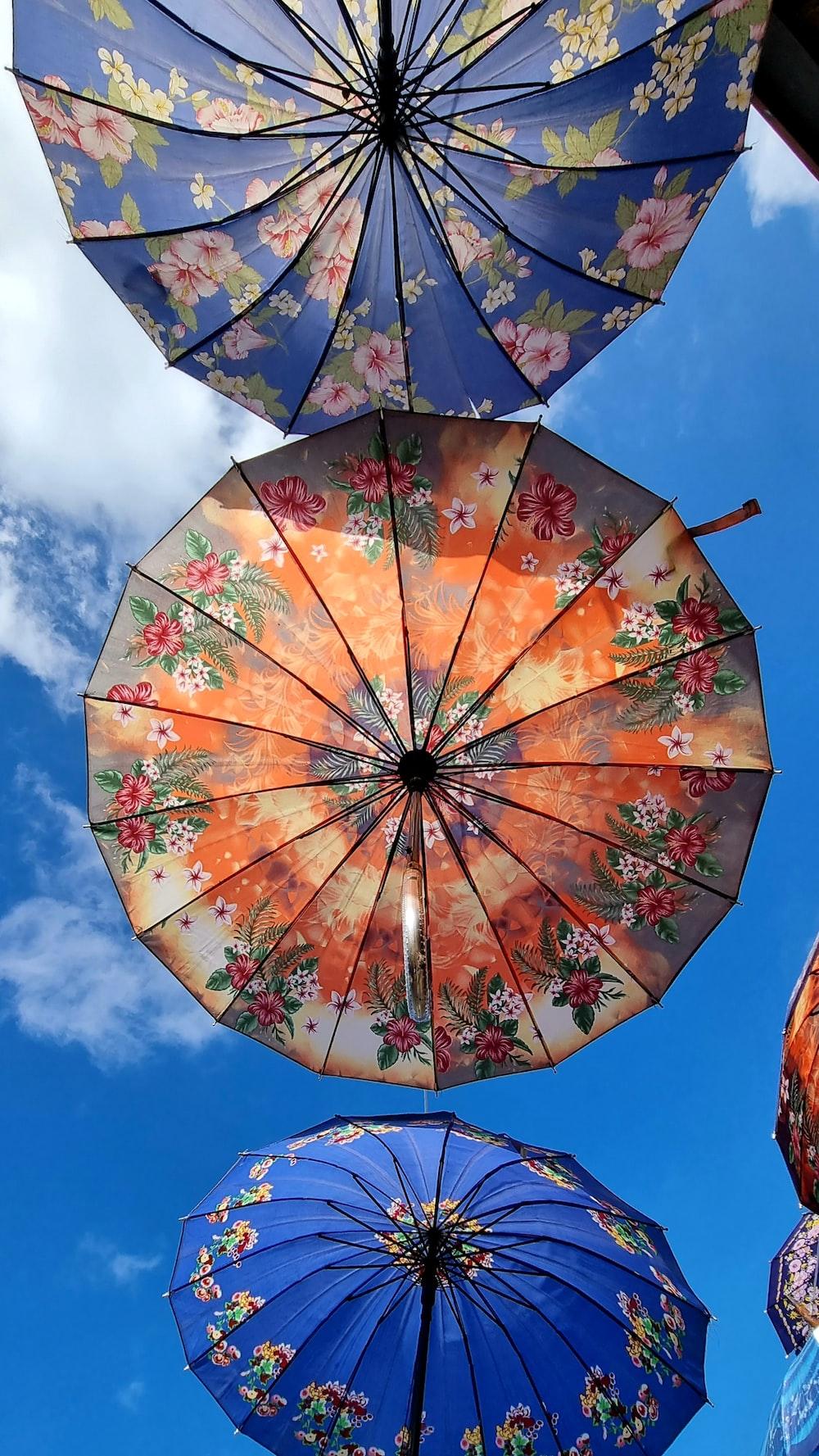 orange and red floral umbrella under blue sky