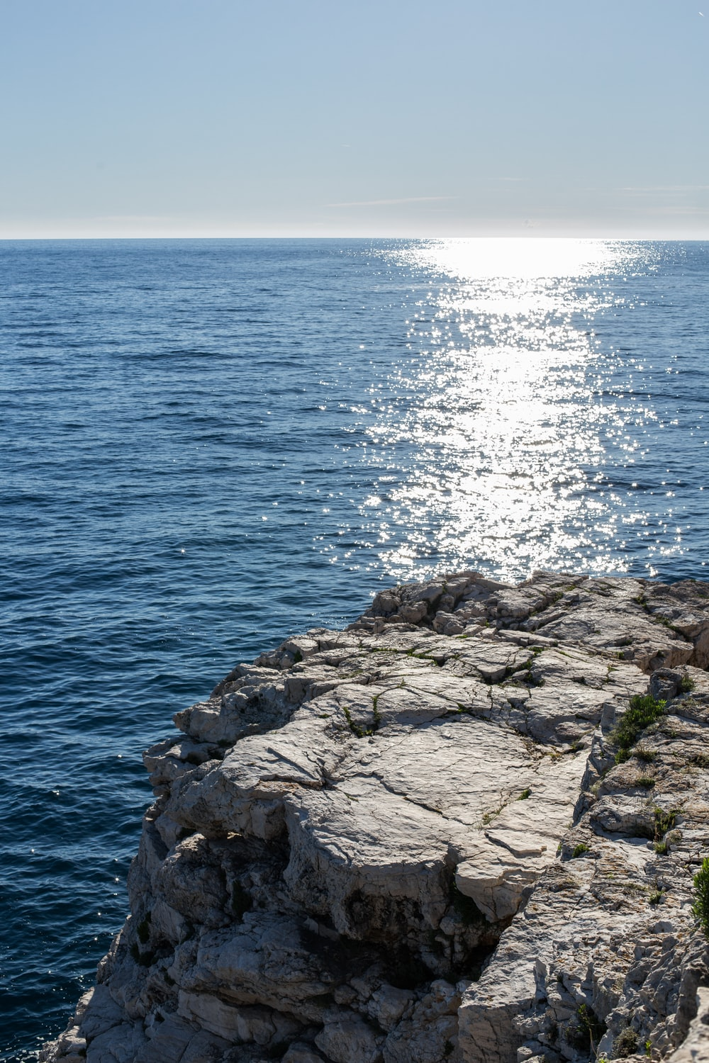 rocky shore with sea waves crashing on rocks during daytime