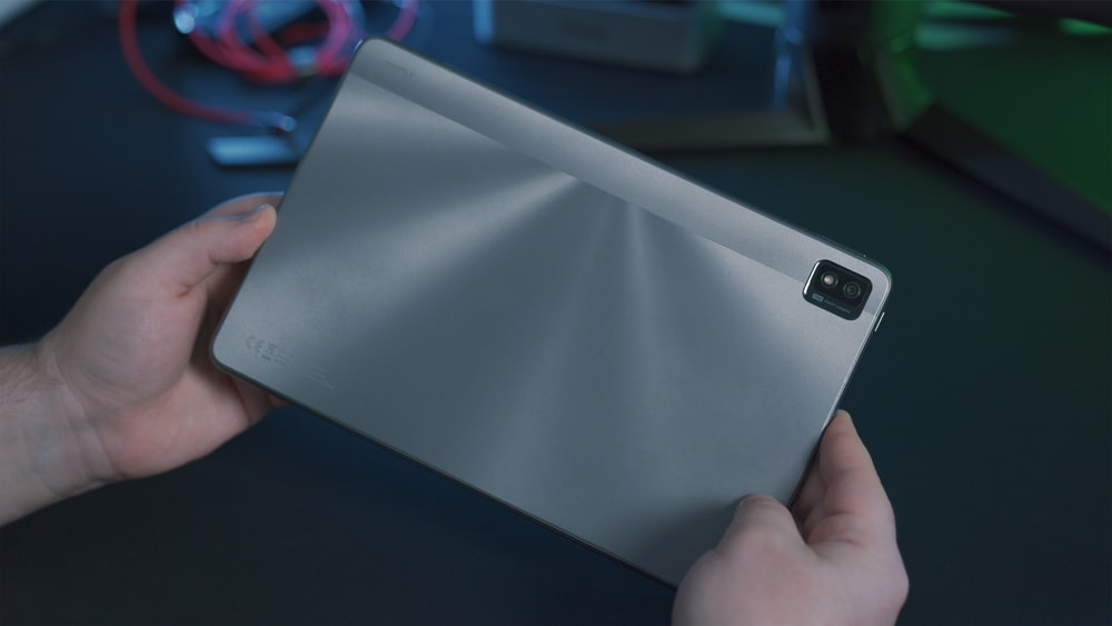 person holding gray tablet computer