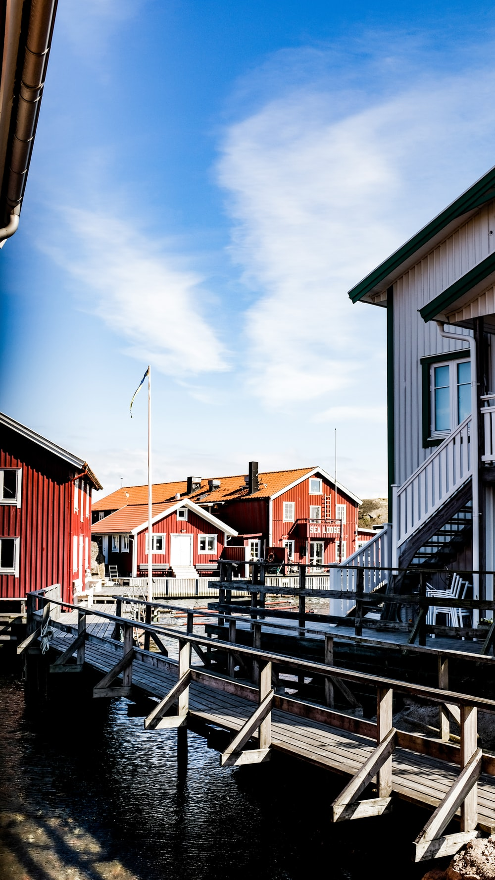red white and blue houses beside body of water during daytime