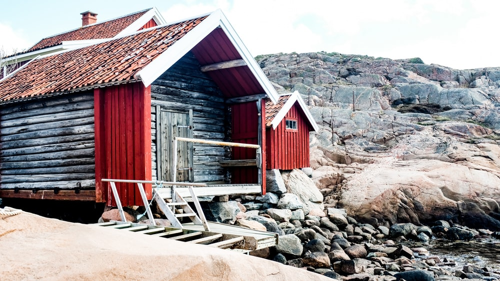 red wooden house near brown rocks