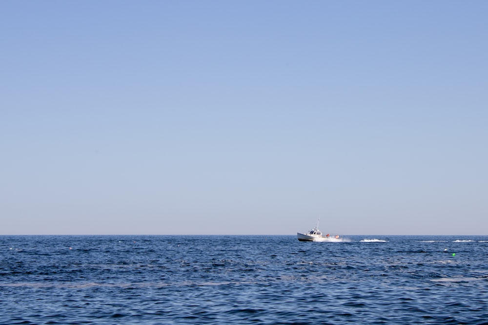 white boat on sea under gray sky during daytime