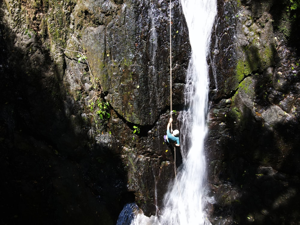 person in blue jacket and blue denim jeans standing on rock near waterfalls during daytime