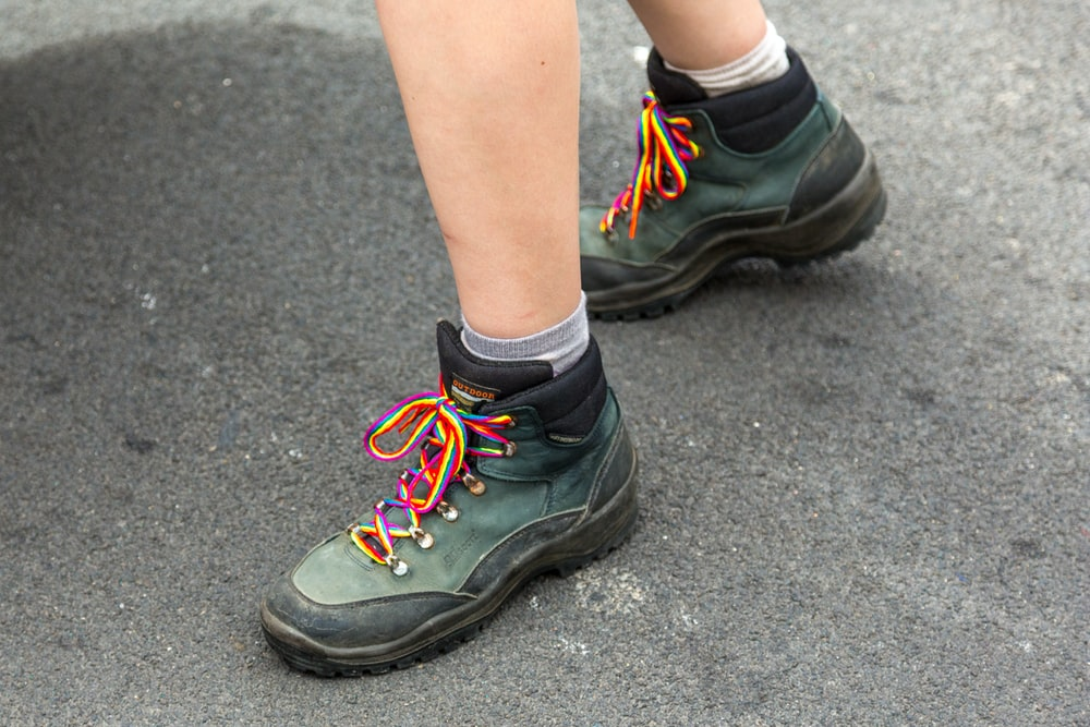 person wearing black and green nike athletic shoes