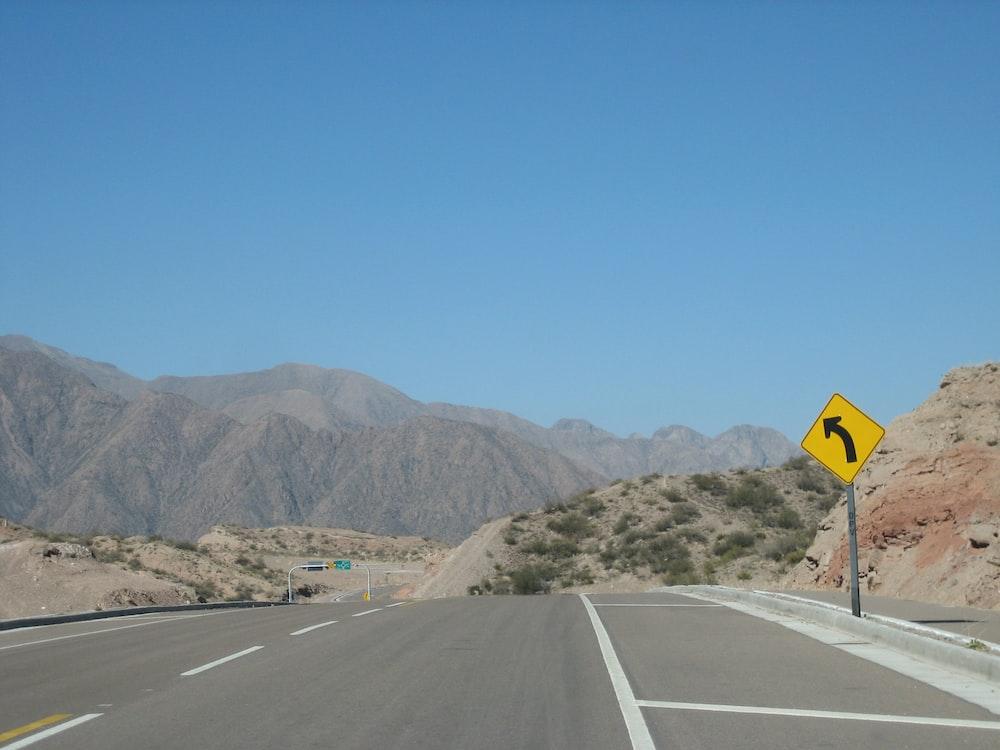 gray concrete road near mountain during daytime