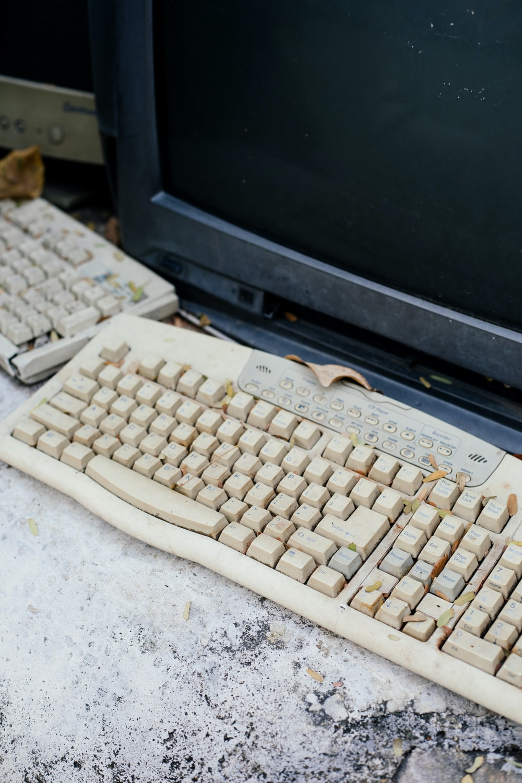 white computer keyboard beside black sony crt tv