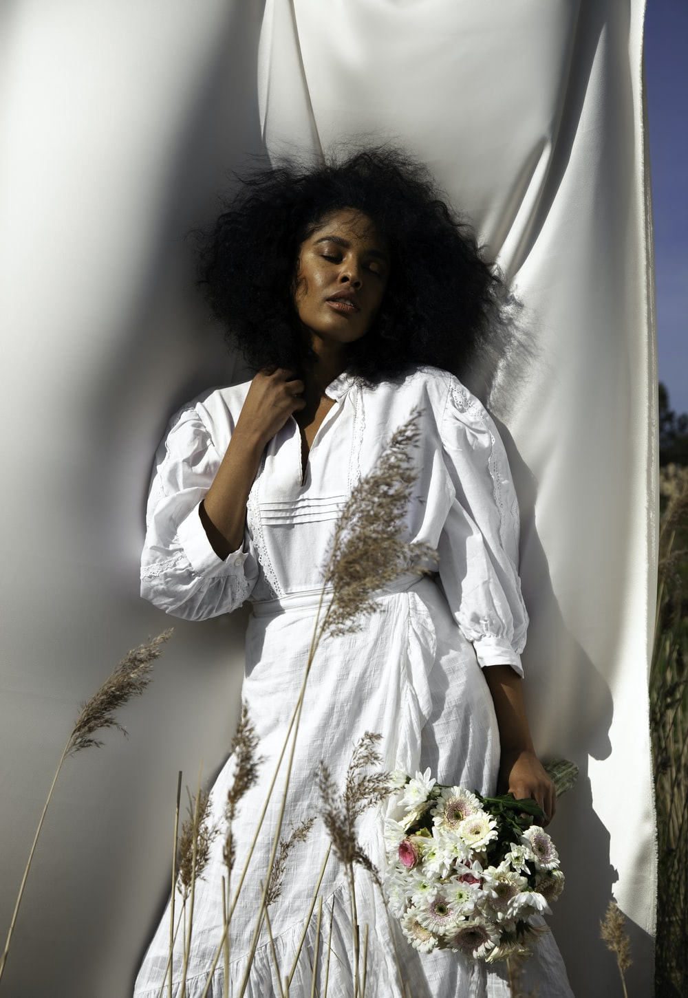 woman in white long sleeve shirt holding white flowers