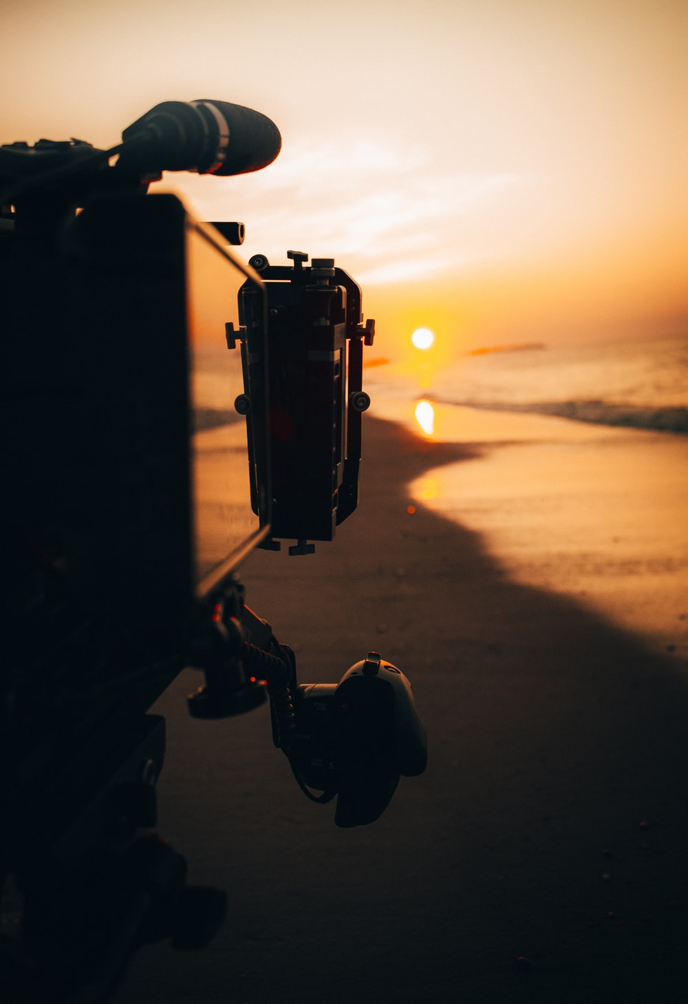 person holding camera during sunset