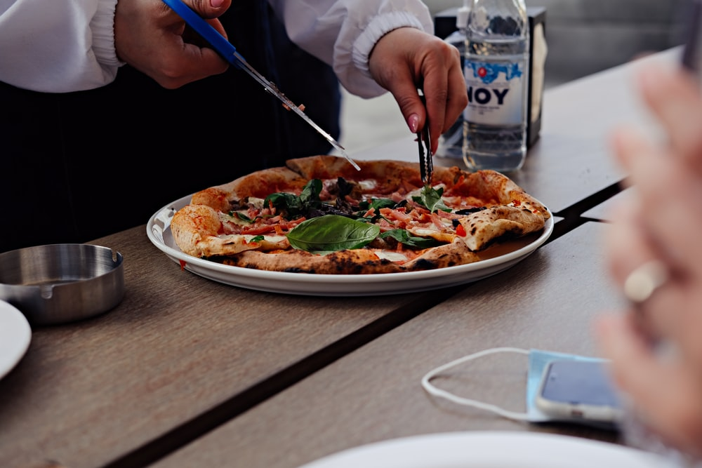 person holding blue and black chopsticks slicing pizza on white ceramic plate